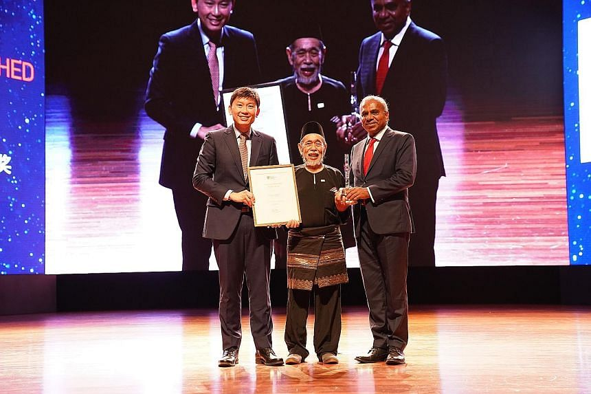 Malay-language literary pioneer Suratman Markasan (centre), one of the three recipients of the Nanyang Distinguished Alumni Award, with Senior Minister of State for Trade and Industry and Education Chee Hong Tat and NTU president Subra Suresh. PHOTO: