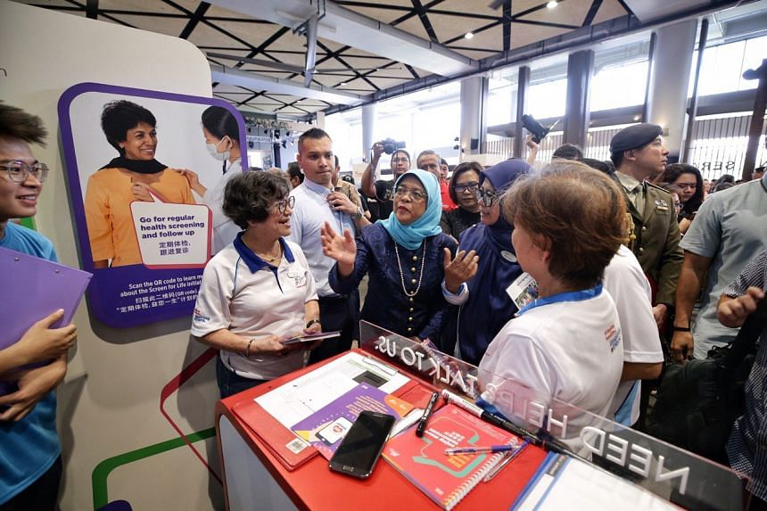 President Halimah Yacob interacting with staff at the Health Promotion Board booth during her tour of the Merdeka Generation roadshow at Wisma Geylang Serai on Oct 20, 2019.
