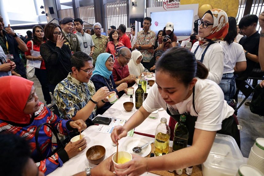 President Halimah, flanked by Senior Minister of State Maliki Osman (left) and Minister Masagos Zulkifli, making a body scrub using essential oils, oil and fine salt on Oct 20, 2019.