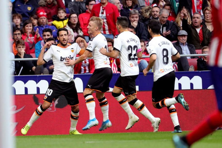 Valencia player Dani Parejo (left) celebrates with teammates after scoring a goal during the Spanish La Liga match held between Atletico Madrid and Valencia FC at Wanda Metropolitano Stadium in Madrid on Oct 19, 2019.