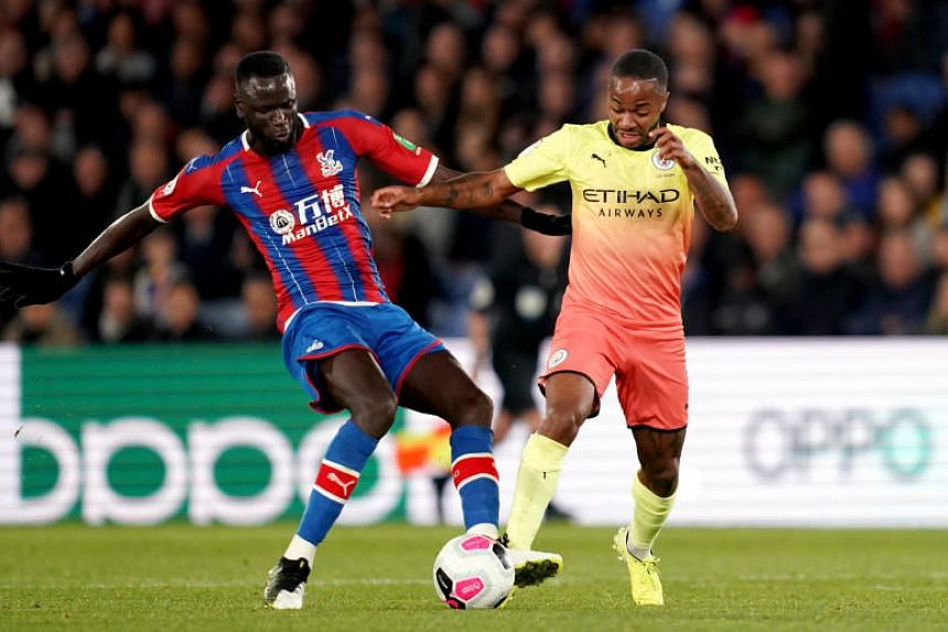 Crystal Palace's Cheikhou Kouyate (left) and Manchester City's Raheem Sterling battle for the ball during the English Premier League soccer match between Crystal Palace and Manchester City at Selhurst Park on Oct 19, 2019.