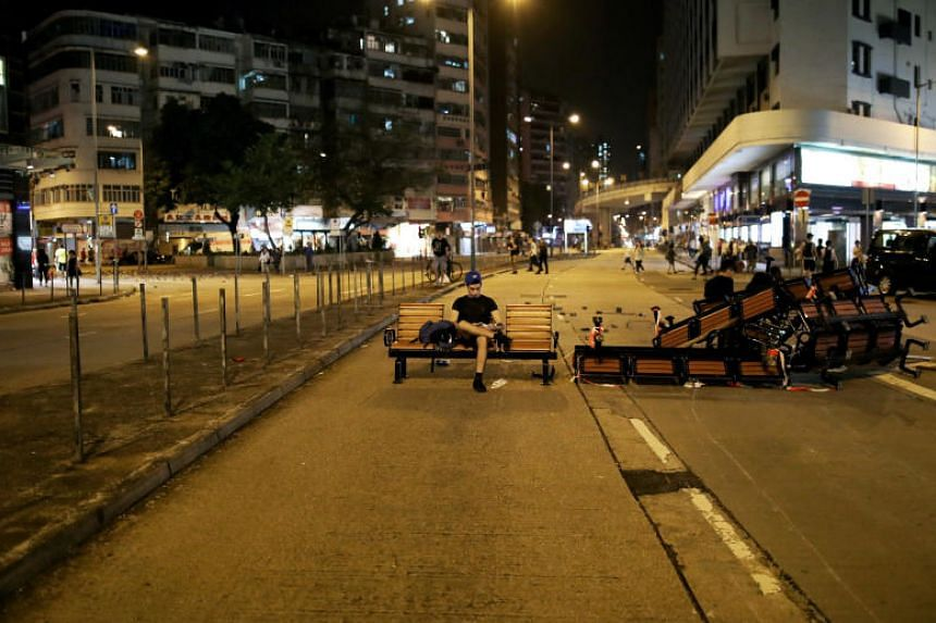 People sit on a barricade made of benches left after a protest in Hong Kong on Oct 20, 2019.