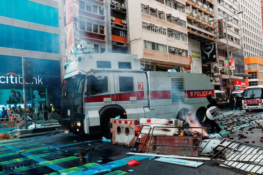 A police water cannon vehicle being driven through a burning barricade in Hong Kong on Oct 20, 2019.