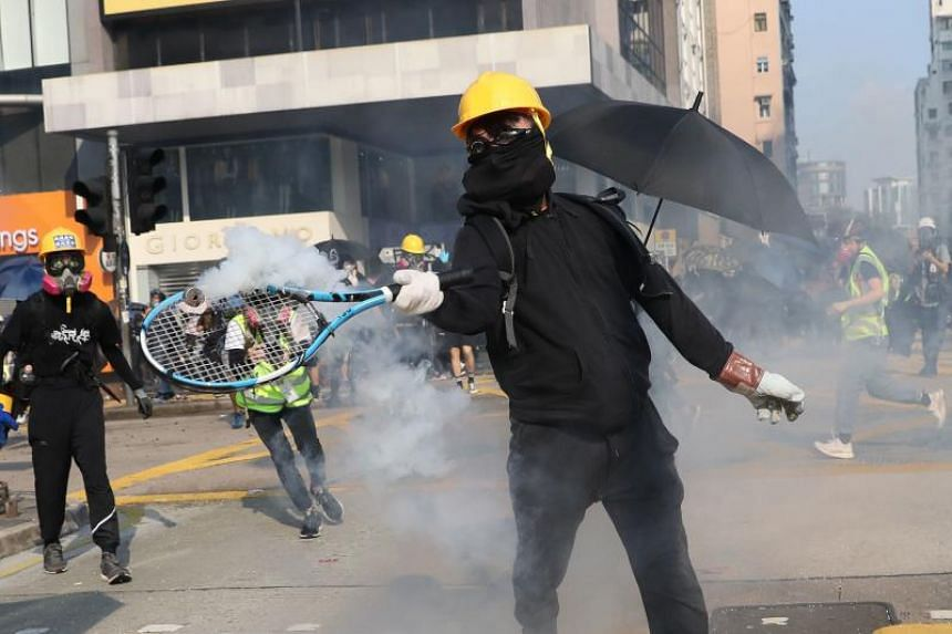A protester hits a tear gas canister with a tennis racket in Hong Kong's Tsim Sha Tsui district on Oct 20, 2019.
