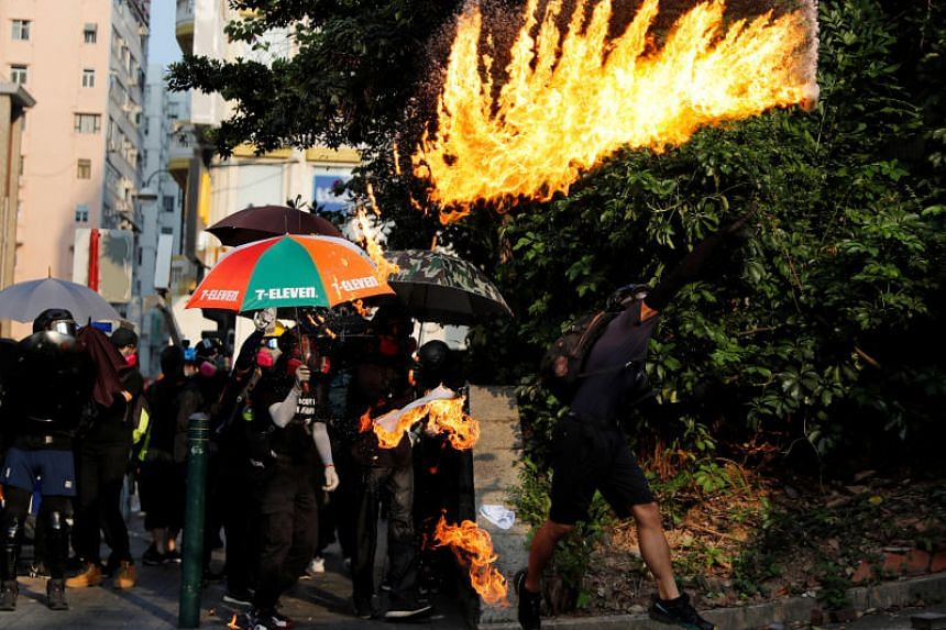A proterster throws a petrol bomb towards Tsim Sha Tsui Police Station in Hong Kong on Oct 20, 2019.