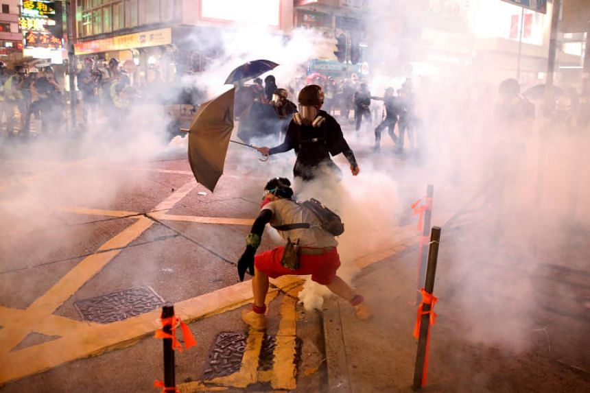 Protesters surrounded by smoke from tear gas fired by police in Hong Kong on Oct 20, 2019.