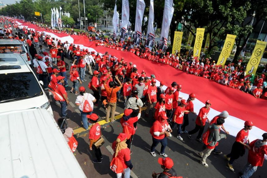 Supporters of Indonesian President Joko Widodo carry a giant Indonesian national flag during Mr Joko's inauguration ceremony in Jakarta.