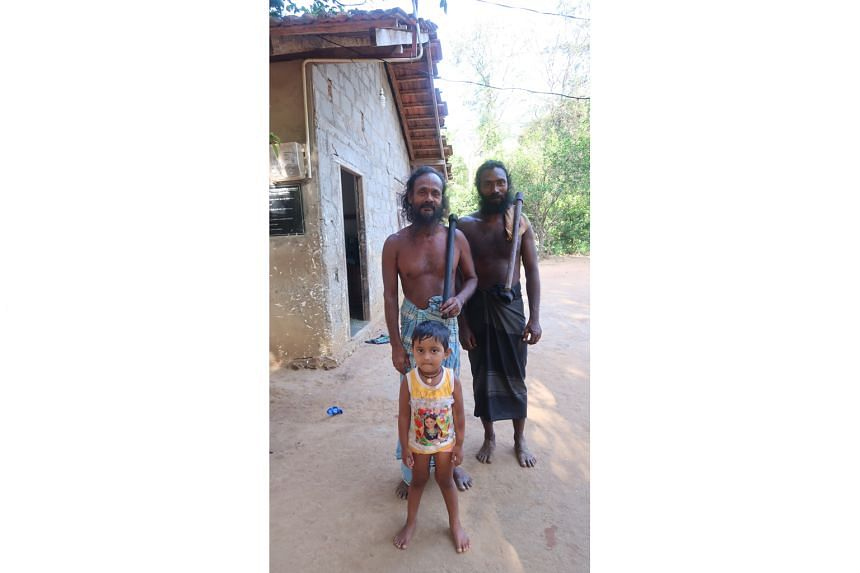 Sudhawaninila (centre), chief of the local Vedda tribe, with his second in command Poromala and his granddaughter.