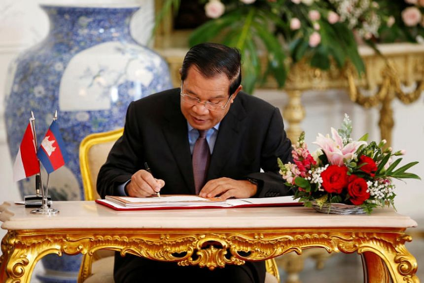 Cambodian Prime Minister Hun Sen signs a guest book during his meeting with Indonesian President Joko Widodo at the Istana Merdeka in Jakarta.