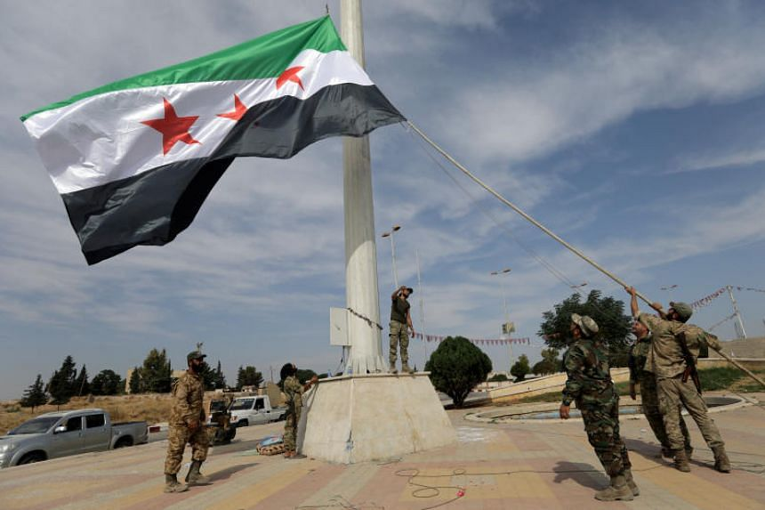 A photo taken on Oct 14 shows Turkey-backed Syrian rebel fighters raising the Syrian opposition flag at the border town of Tel Abyad in Syria.