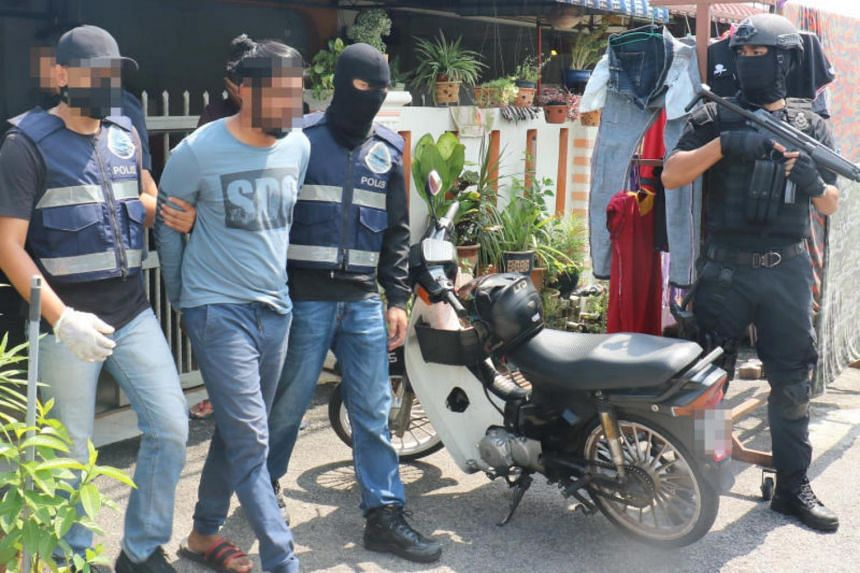 A photo taken on Oct 12 shows Malaysia's counter-terrorism police arresting one of five men over alleged links to the defunct Liberation Tigers of Tamil Eelam.