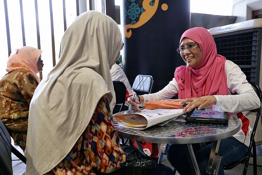 Madam Jamalbi Abdul Hameed (right) attending to a resident at the roadshow in Wisma Geylang Serai yesterday. She has been a Silver Generation ambassador since 2014 and it involves reaching out to seniors at their homes to explain government schemes s