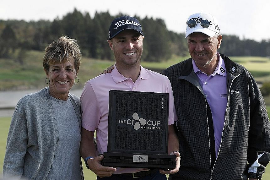 Justin Thomas of the United States, with mother Jani and father Mike after winning the CJ Cup in Jeju Island yesterday. His parents had flew over from Louisville to watch him play in the tournament.