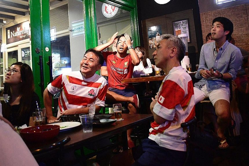 "Japanese fans at Thunderbird Bistro in Robertson Walk watching yesterday's World Cup quarter-final game. One supporter said: ""We are disappointed but not sad because we are among the best eight teams."""