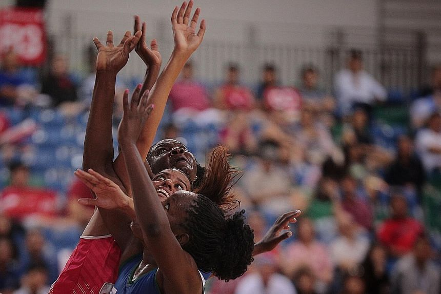 Singapore's Sindhu Nair is sandwiched between two Namibia players as she fights for a rebound in yesterday's M1 Nations Cup netball tournament at the OCBC Arena.