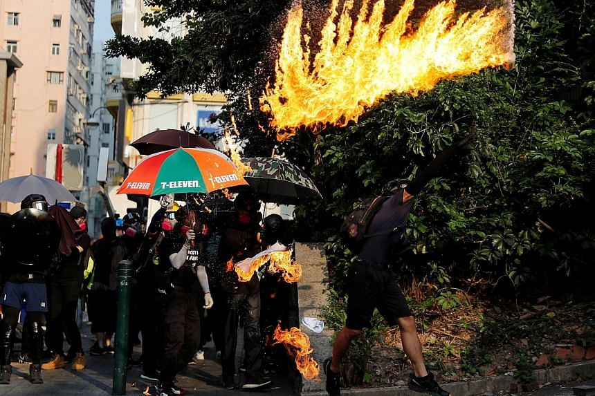 An anti-government protester throwing a petrol bomb towards the Tsim Sha Tsui police station during a protest in Hong Kong yesterday. PHOTO: REUTERS