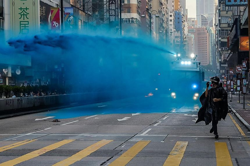 A protester running from an advancing police water cannon as it sprayed water laced with blue dye and chemicals in Tsim Sha Tsui district yesterday. At Tsim Sha Tsui Police Station, police fired multiple volleys of tear gas while warning protesters o