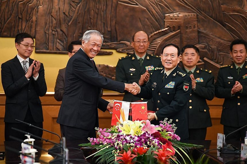 Defence Minister Ng Eng Hen and his Chinese counterpart Wei Fenghe (right) after the signing of the enhanced defence pact yesterday in Beijing. PHOTO: MINDEF