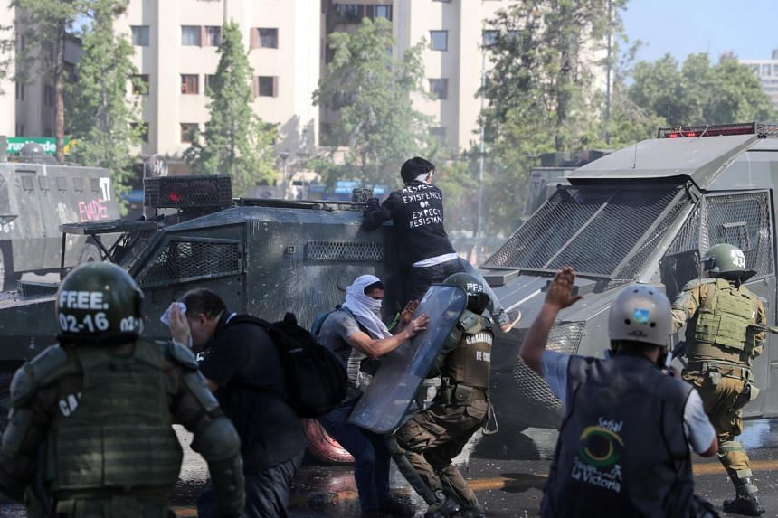 Protesters clash with riot police officers during a protest in Santiago, Chile, on Oct 20, 2019. The capital and other Chilean cities have been engulfed by several days of riots.