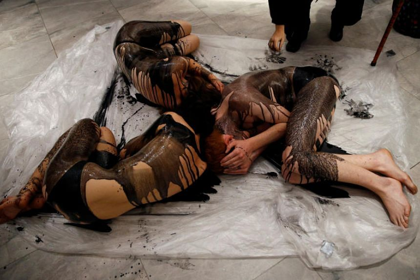 Extinction Rebellion members lie on the ground, covered in fake crude oil, to protest an exhibition sponsored by BP at The National Portrait Gallery in London, Britain, on Oct 20, 2019.