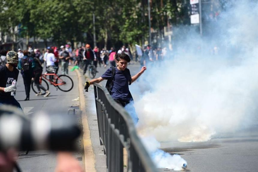 Demonstrators clash with riot police during protests in Santiago, on Oct 20, 2019.