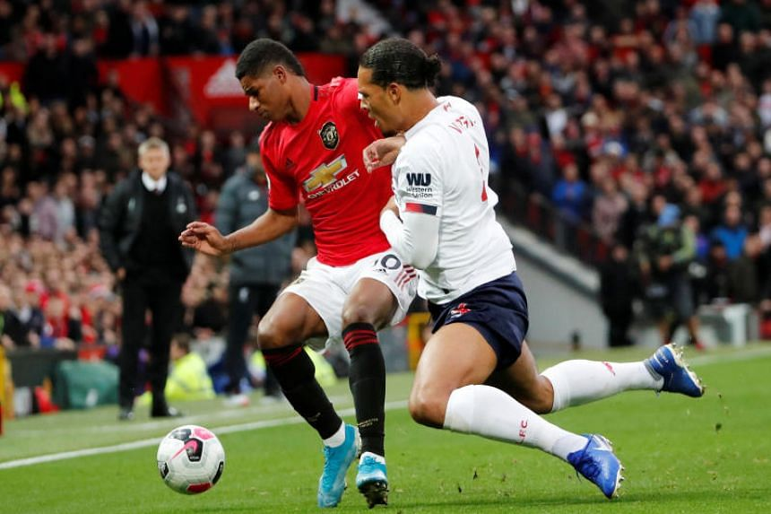 Liverpool's Virgil van Dijk in action with Manchester United's Marcus Rashford.