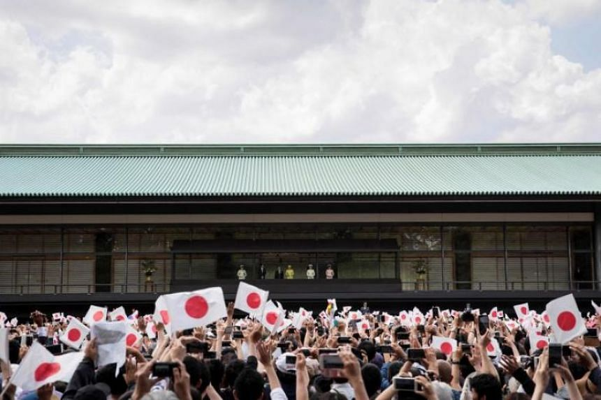 In a photo taken on May 4, well-wishers wave Japanese flags as Japan's Emperor Naruhito and Empress Masako make their first public appearance after ascending to the throne along with other members of the royal family at the Imperial Palace in Tokyo.