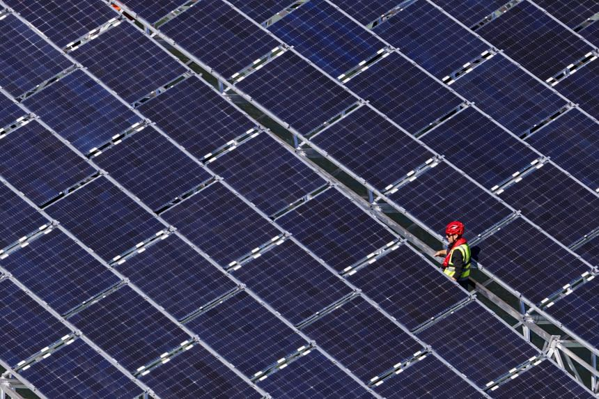 A worker assembling floating barges with solar panels in Bourg-Saint-Pierre, Switzerland, on Oct 8, 2019.