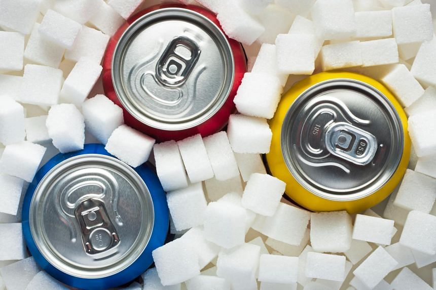 Carbonated drinks surrounded by sugar cubes.