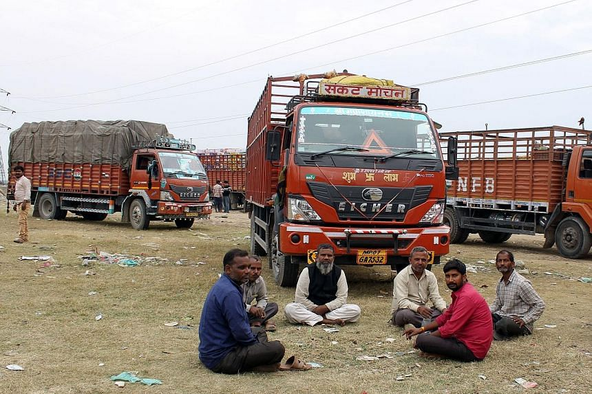 Public bus drivers sitting around the old bus depot in Kashmir's capital Srinagar. They have refused to drive as a mark of protest against the Indian government's decision to revoke the region's seven decades of constitutional autonomy. Dal Lake is c