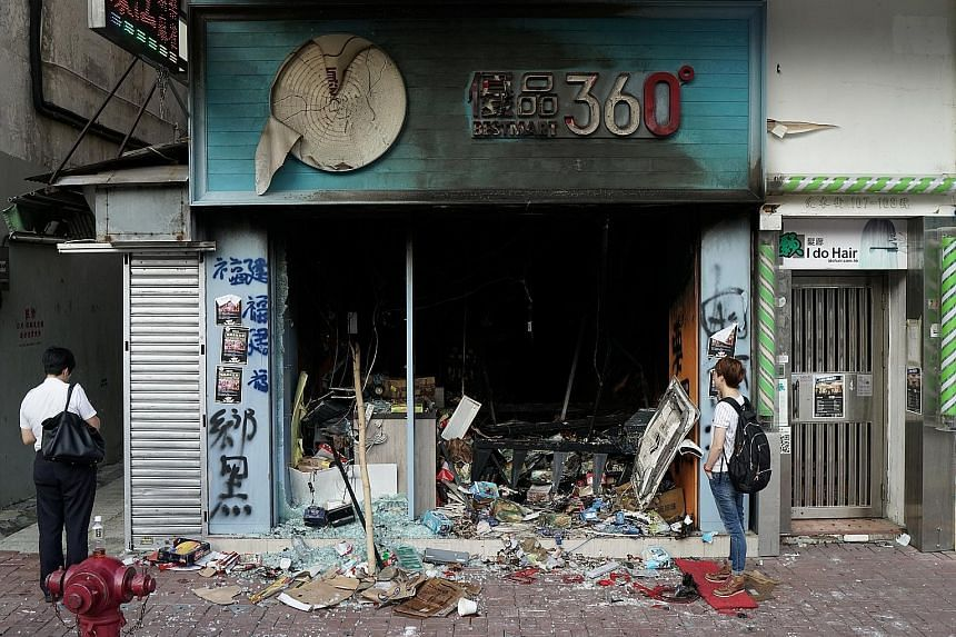 A store that was vandalised on Sunday by protesters. Opinion remains divided on what impact the continuing unrest will have on businesses. PHOTO: REUTERS A protester hurling a petrol bomb into the Tsim Sha Tsui Police Station (left), and another vand
