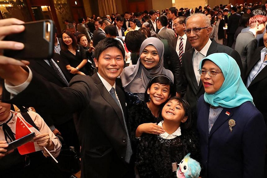Singapore President Halimah Yacob and her husband, Mr Mohamed Abdullah Alhabshee, posing for a wefie with Yomiuri Shimbun political writer Keita Ikeda and his Singaporean wife, Dr Rita Zamzamah Nazeer, an assistant professor in English-language studi