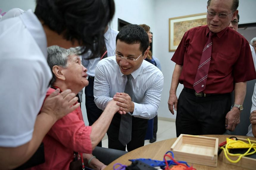 Minister for Social and Family Development Desmond Lee (centre) speaks to a dementia patient at the St John Singapore Dementia Centre on Oct 22, 2019.