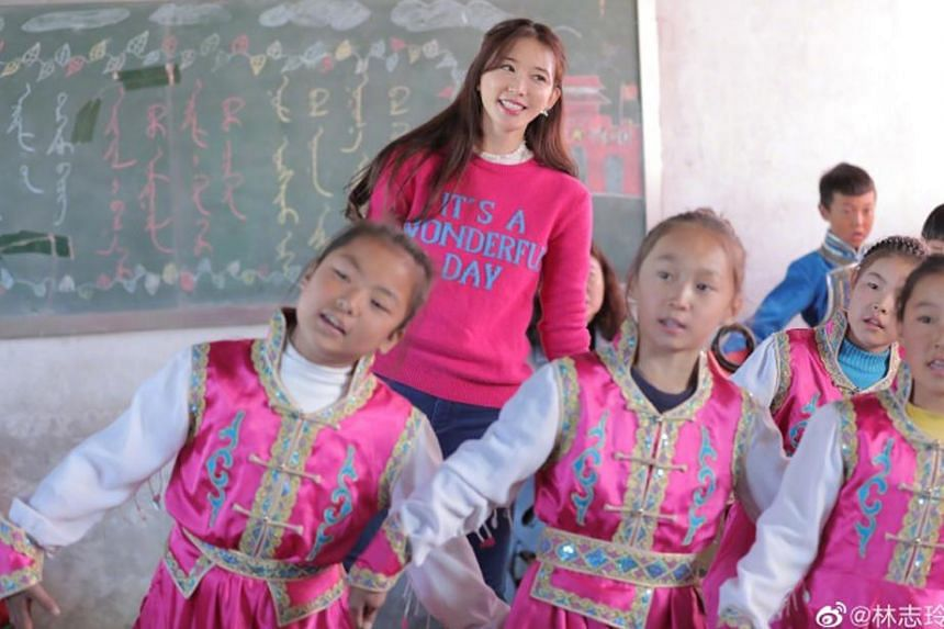 Taiwanese model-actress Lin Chi-ling dances with kids at a children's home in Inner Mongolia, China.