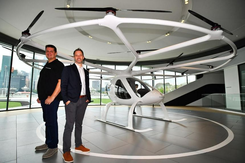 Co-founder of Volocopter Alexander Zosel (left), and CEO of Volocopter Florian Reuter, pose in front of the Volocopter 2X in the VoloPort on Oct 22, 2019.