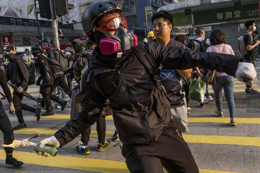 A demonstrator throws a fire bomb in Hong Kong. Protests often feature a darker, anti-China tone, sparking fears among professionals from the mainland who number more than one million among the city's 7.5 million population.