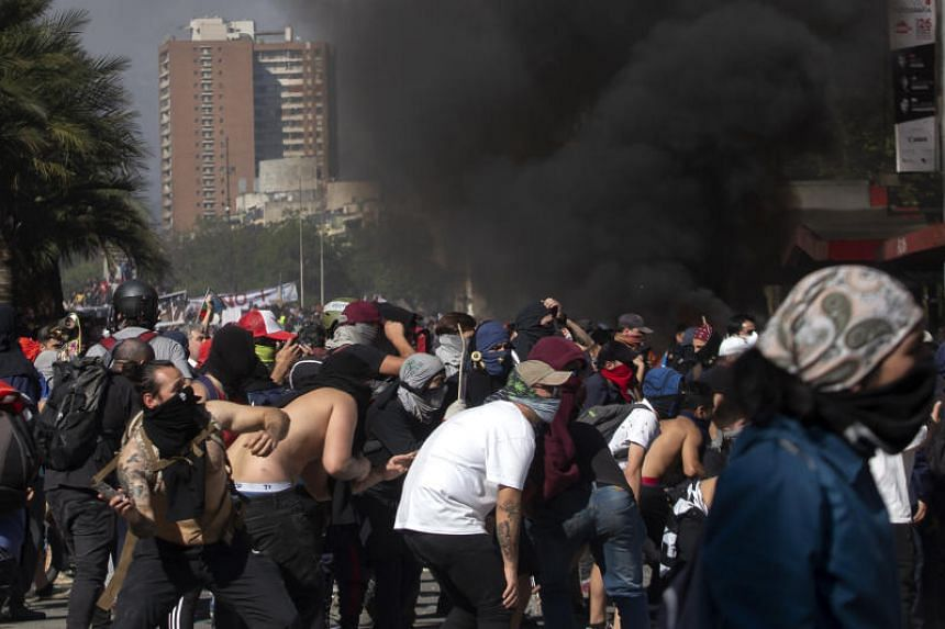 Demonstrators clash with riot police as part of protests against a now suspended hike in metro ticket prices in Santiago, Chile, on Oct 21, 2019.