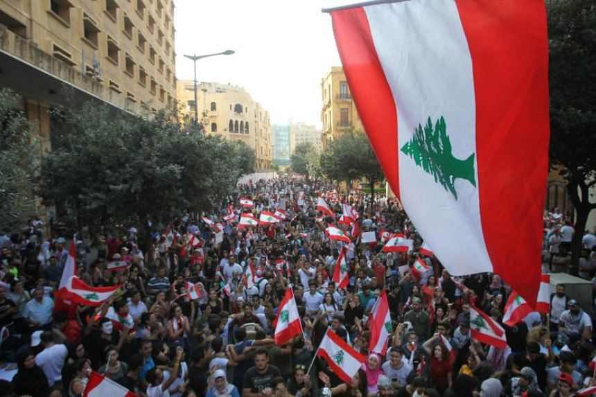 Lebanese demonstrators take part in a protest against dire economic conditions on Oct 21, 2019.