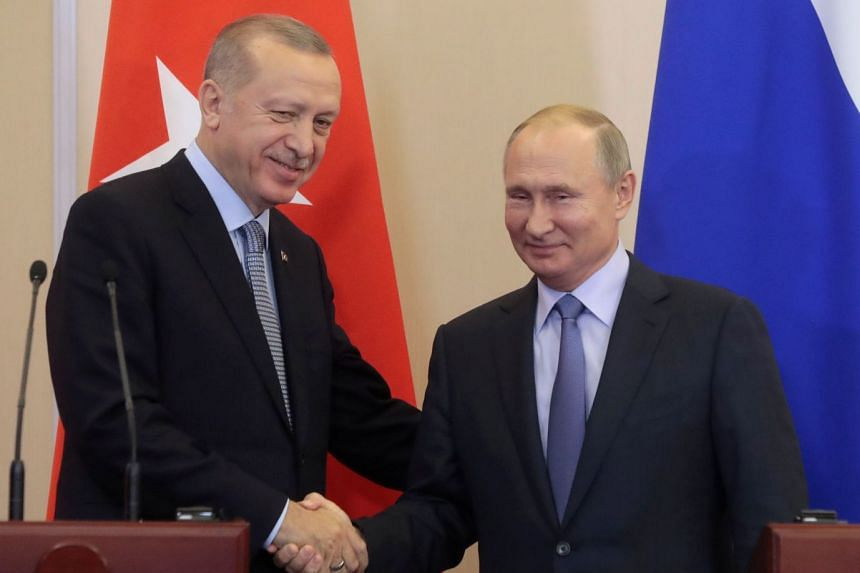 Erdogan (left) and Putin shake hands during a joint press conference following their talks.