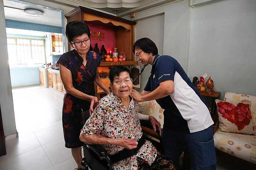 """Ms Madeline Tan (far left), 63, gets help to manage her 86-year-old mother's chronic conditions under the """"Integrated General Hospital"""" pilot care model. She regularly sends Madam Soh Lai Hong's blood pressure and diabetes readings to Alexandra Hospi"""