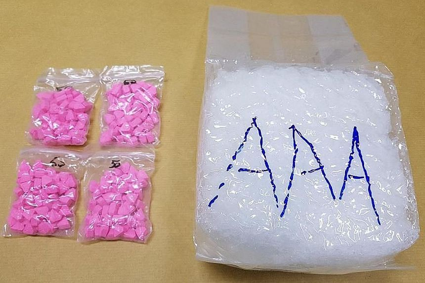 The authorities found 198 Ecstasy tablets and 1.041kg of Ice concealed in the air filter box in the bonnet of a car driven by a 34-year-old Malaysian man at Woodlands Checkpoint on Monday. PHOTO: CENTRAL NARCOTICS BUREAU