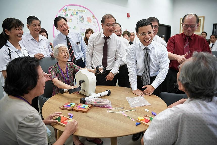 Social and Family Development Minister Desmond Lee (standing, second from right) speaking to seniors at St John Singapore Dementia Centre yesterday, when the centre was officially launched.