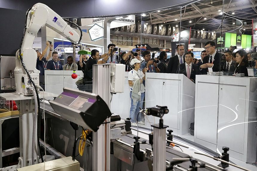 Deputy Prime Minister Heng Swee Keat looking at the next-generation hyper-personalised factory line at the Industrial Transformation Asia-Pacific trade show yesterday. Mr Heng stressed the importance of having a conducive environment for technology i