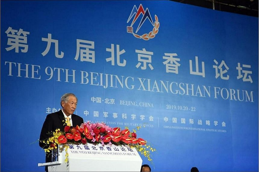 Defence Minister Ng Eng Hen speaking at a plenary session on the interests of small and medium-sized states at the Beijing Xiangshan Forum yesterday. He said the world needs both the US and China to work together to ensure progress and stability, and