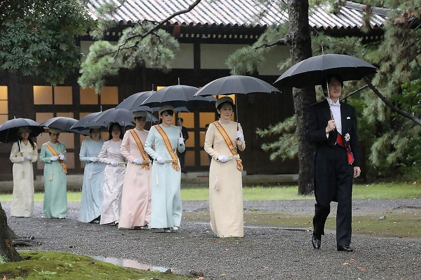 Japan's Emperor Naruhito proclaiming his enthronement from the platform of the Takamikura throne yesterday. His wife, Empress Masako, took the slightly shorter Michodai platform. PHOTO: EPA-EFE President Halimah Yacob and Iceland's President Gudni Th