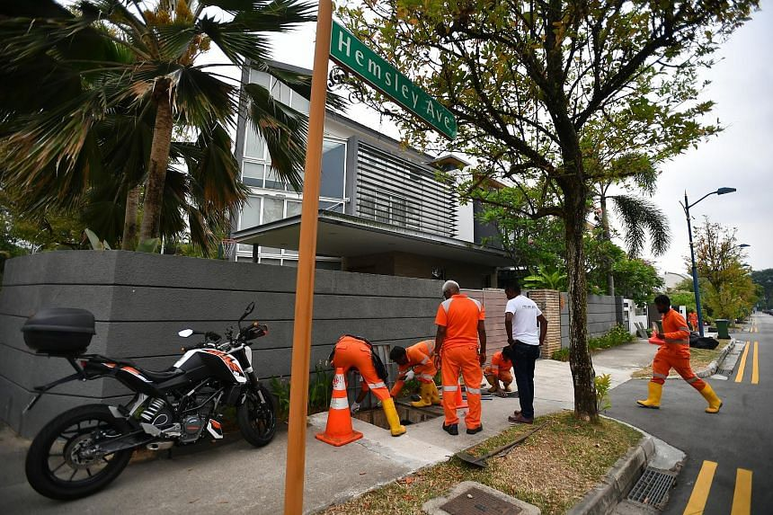 Workers clearing the drains in Serangoon Gardens last month as part of the efforts to fight dengue. Singapore saw a 13-week downward trend in the number of reported dengue cases until the week ending Oct 12, but the NEA urged continued vigilance due
