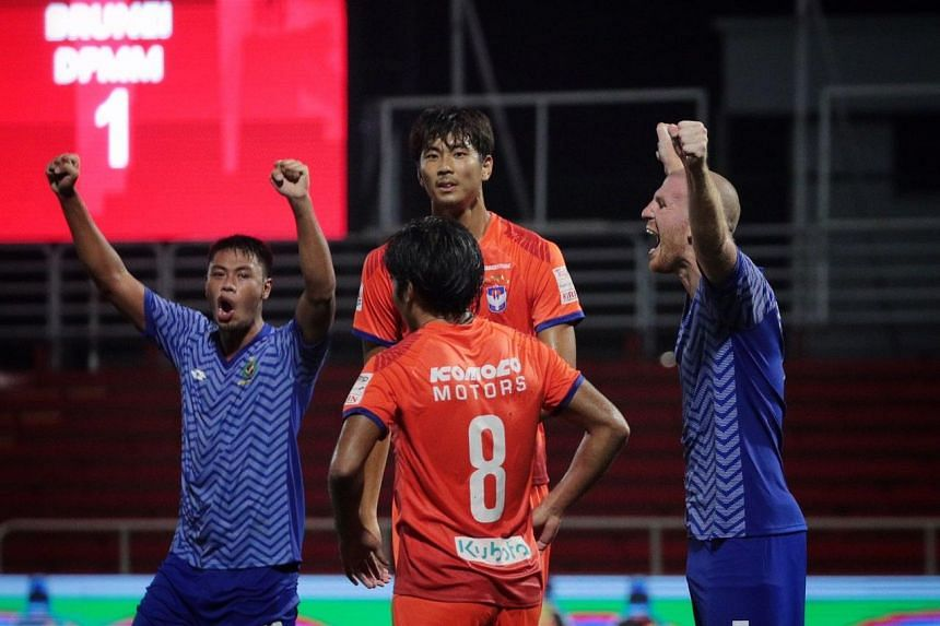 Brunei DPMM's Yura Indera Putera and Charlie Clough (left and right, in blue) after emerging victorious against Albirex Niigata during their Komoco Singapore Cup match at Jurong East Stadium on Oct 23, 2019.