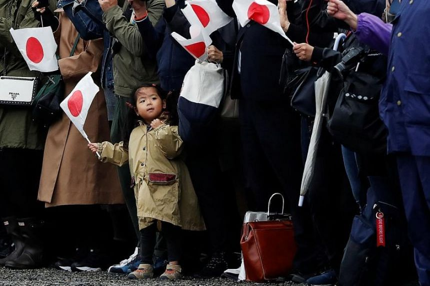 A girl waiting outside the Imperial Palace in Tokyo yesterday. The formal declaration at the enthronement is part of a year-long series of ceremonies that will end in April next year.