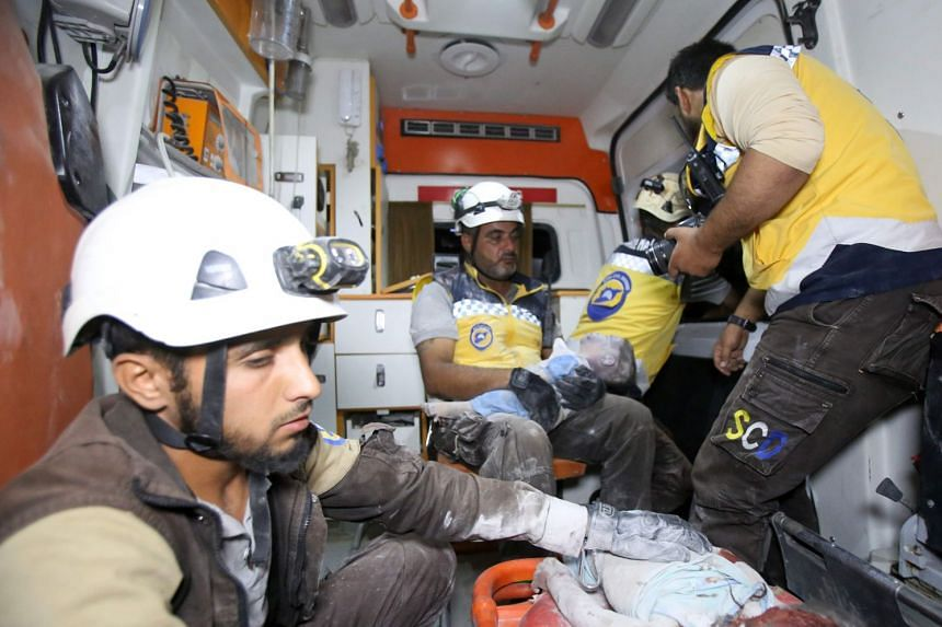 """""""White Helmets"""" transport young victims in an ambulance following a reported airstrike by Syrian regime forces on the town of Maaret al-Numan in Syria's northwestern Idlib province on Aug 28, 2019."""