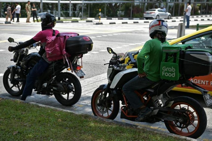 Food Panda and Grab delivery riders waiting at a traffic light along South Buona Vista Road on Oct 15, 2019.